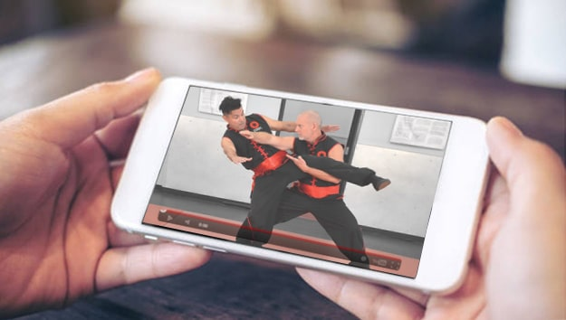 Image of someone accessing Combat Kung-Fu's online self-defense courses from an iPhone.