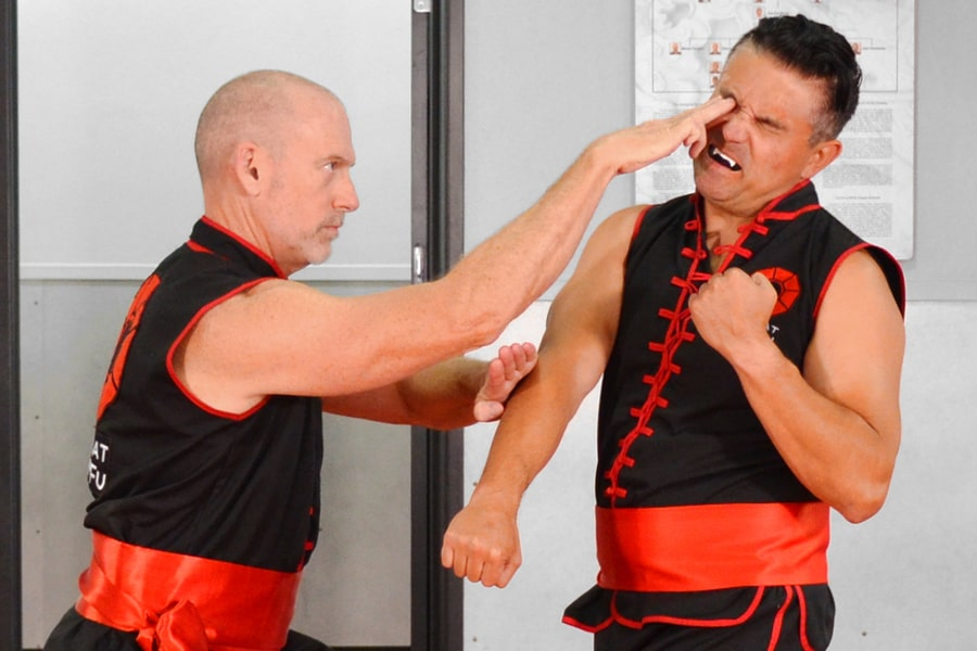 Image of Master Fisher, Founder of Combat Kung-Fu, showing how a blinding technique can disable a much bigger and stronger attacker.