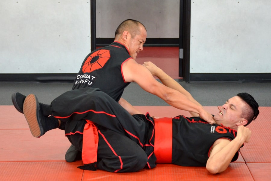 Ground fighting is integral to mastering the art of self-defense. Here Sifu Ming Lau fights his way out of a guard position using Choy Li Fut's level fist strike to the throat.